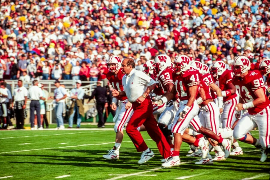 Barry Alvarez runs across field with Badger football team during the 1994 Rose Bowl game