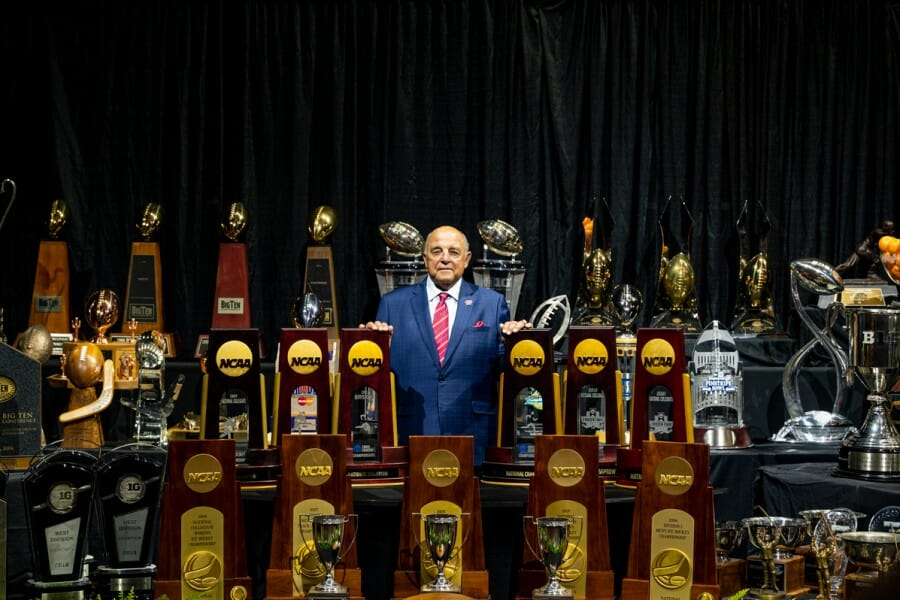 Barry Alvarez poses amidst all of the trophies won during his tenure as UW Athletics Director