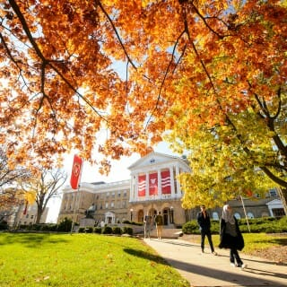Students walk along a colorful tree-lined sidewalk outside Bascom Hall in fall