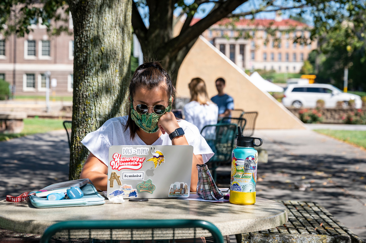 Student wearing face mask works on laptop outside