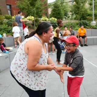 Woman and child dance at the Multicultural Summer Picnic at Alumni Park