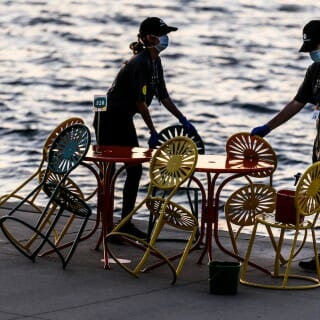 Wisconsin Union staff clean and sanitize tables and sunburst-designed chairs in between patrons enjoying physically distanced, reserved-table seating with food and drink service at the Memorial Union Terrace