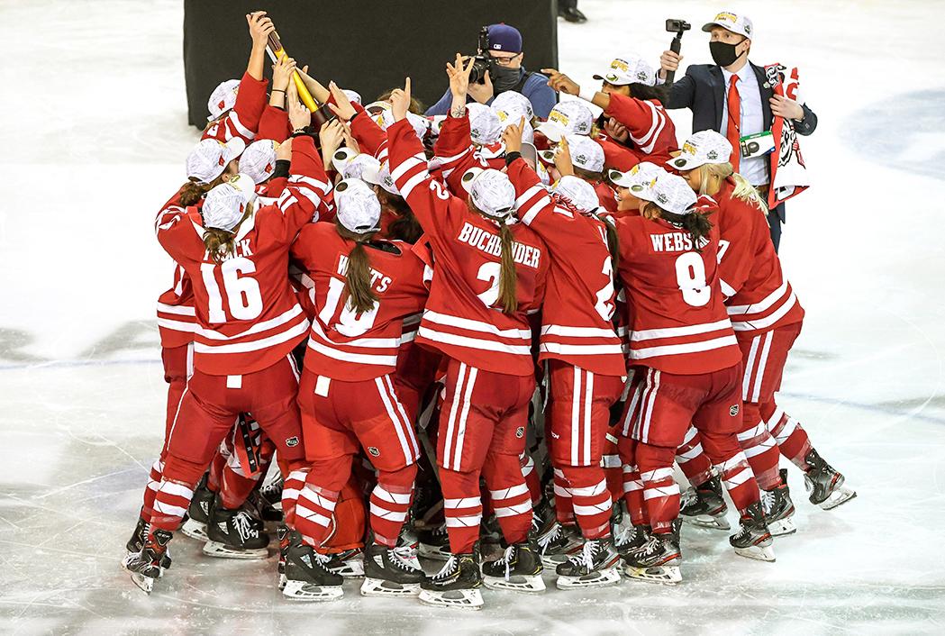 UW Women's hockey team embraces on the ice