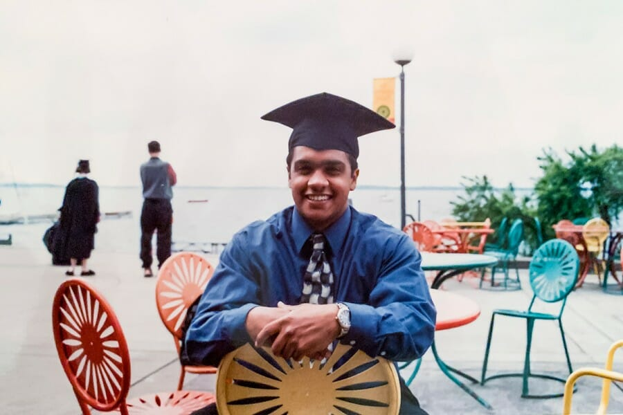 A young Raju sitting at the Memorial Union Terrace wearing a graduation cap