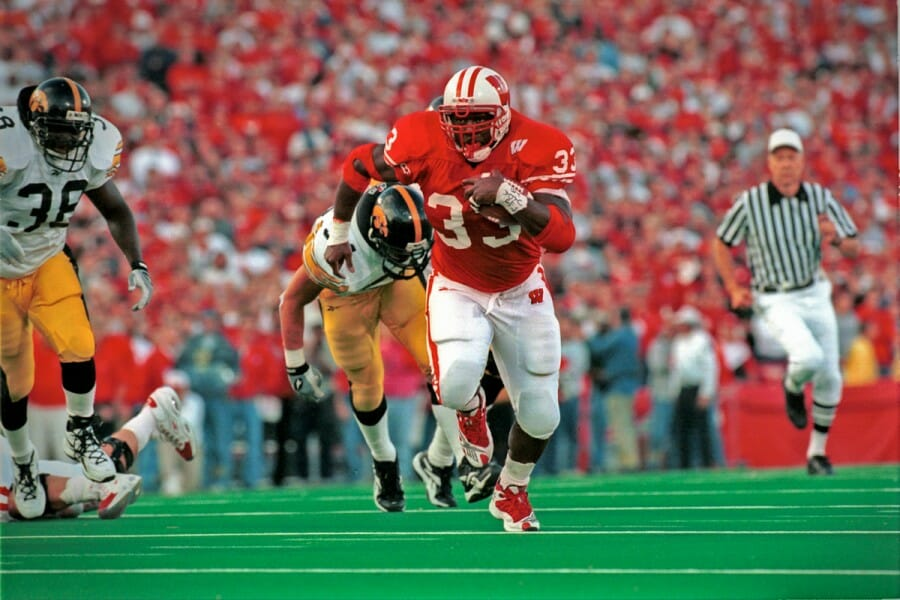 Ron Dayne rushes with football during 1999 Iowa game