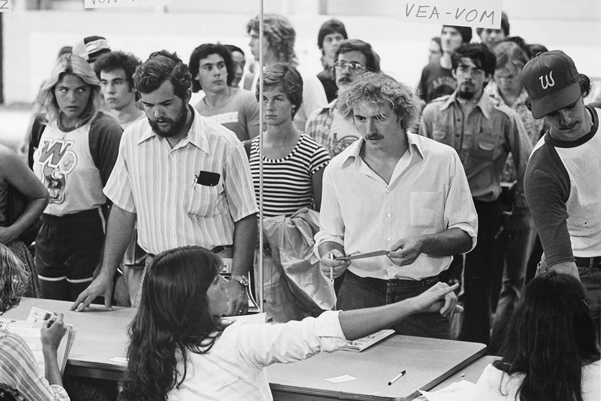 1980s black and white photo of students waiting in line at a table to register for classes