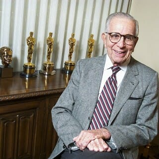 Walter Mirisch with several Academy Awards statuettes