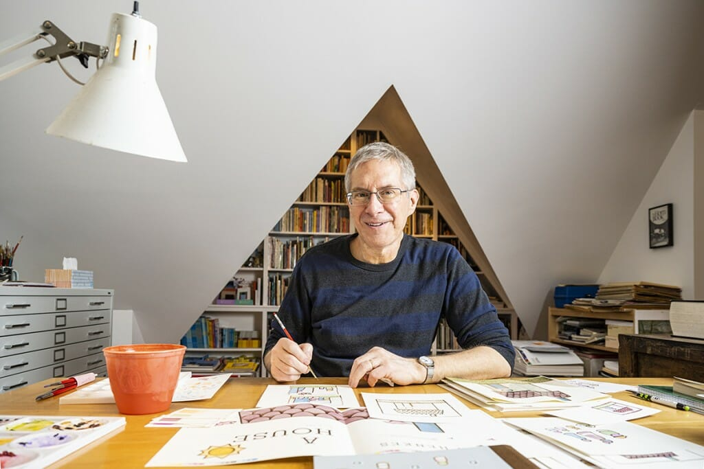 Kevin Henke at his desk with his illustrations