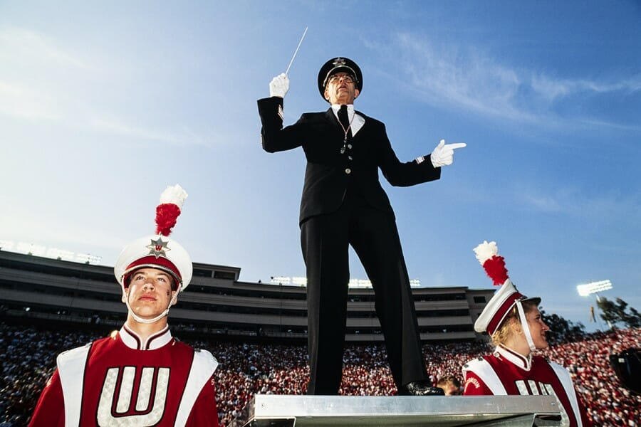 1994 photo of Mike Leckrone leading the UW Marching Band flanked by two band members in their uniforms
